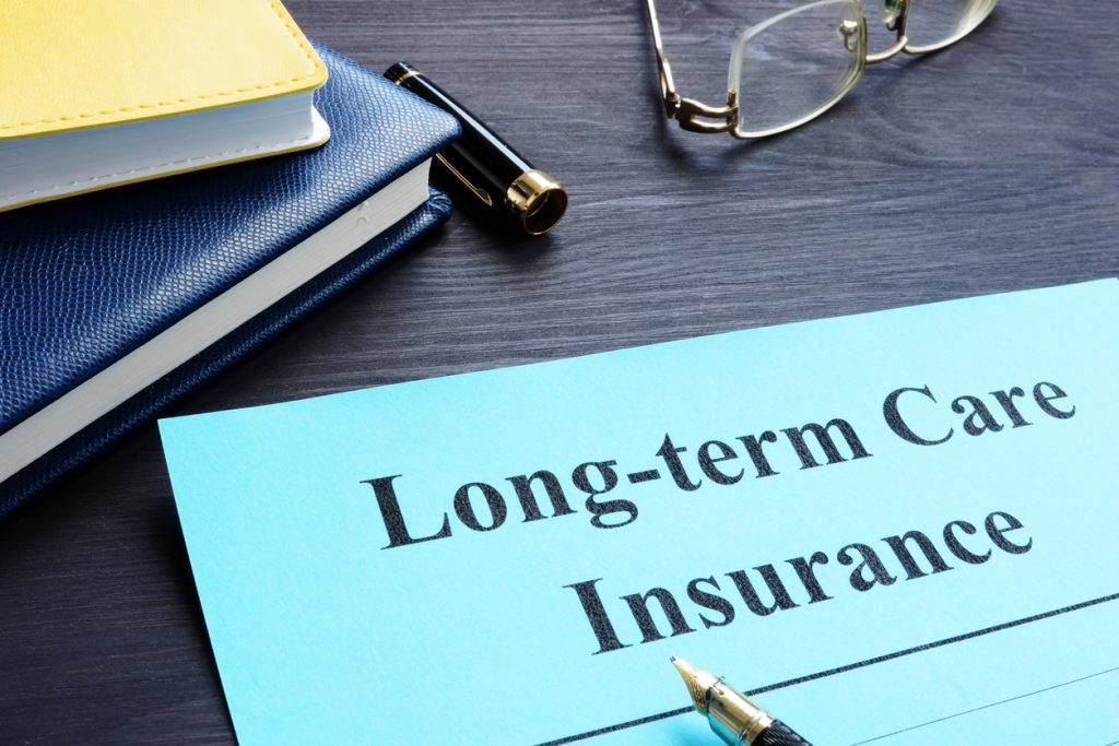 """Blue paper on a desk with the words """"Long-term Care insurance"""" at the top. Traditional long-term care insurance is good for ltc planning."""