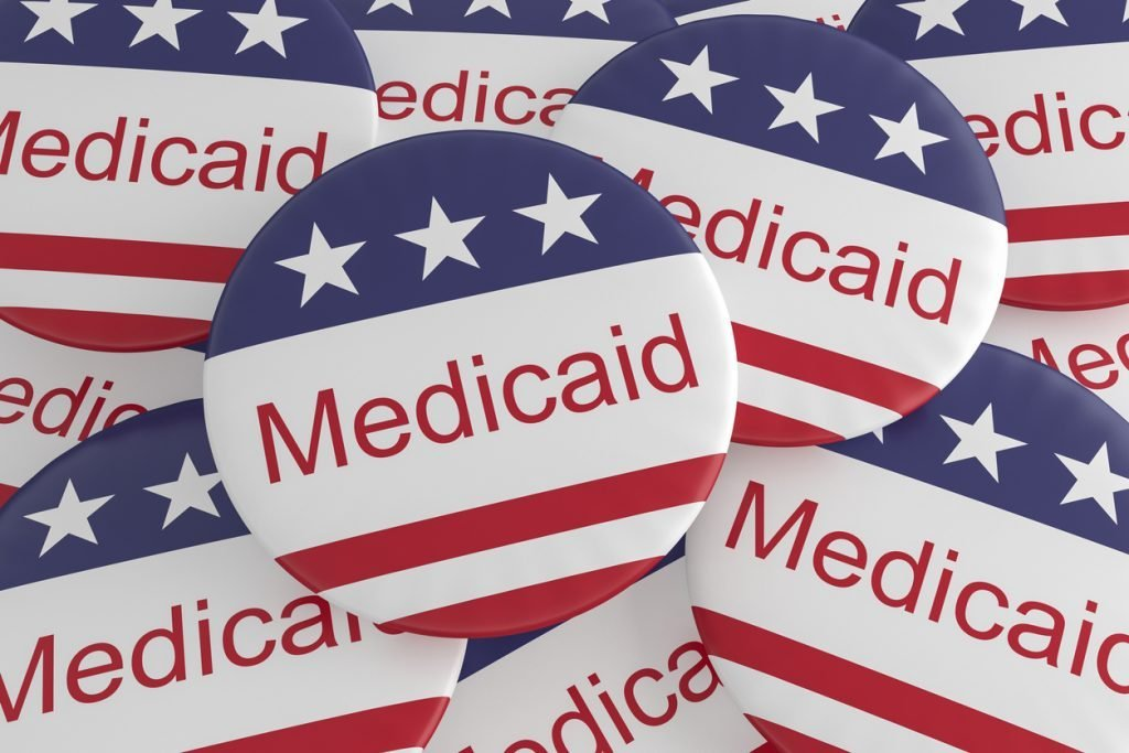 Button pins with the word Medicaid and the American flag.