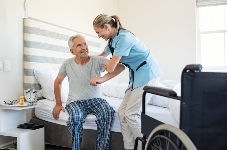 Home Health Care Worker Assisting Elderly Man Transfer Out of Bed  Assisted by a Nurse