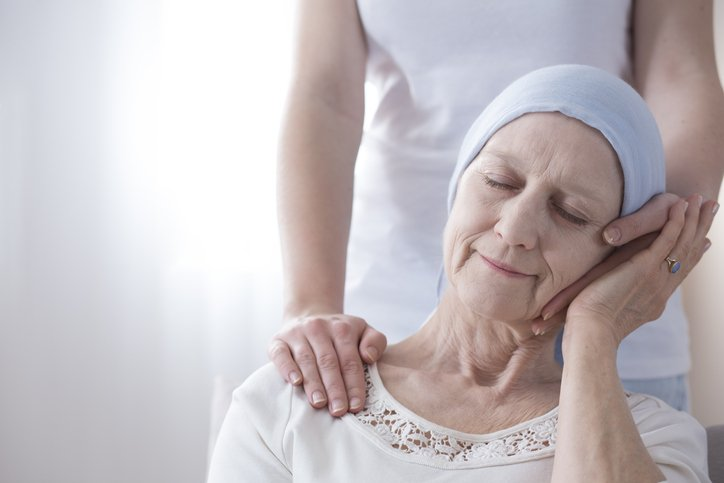 Elderly Woman with Cancer Being Comforted by Hospice Staff Member