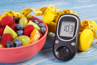 Glucose meter next to bowl of fruits