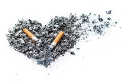 Two Smoking cigarettes lying on tobacco ash. Tobacco ash is scattered in the form of a stylized heart. Concepts: danger of Smoking; do not smoke. Isolated on white.