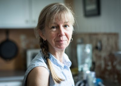 Retirement age woman doing home improvement standing in a kitchen