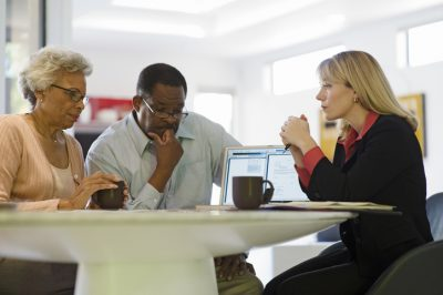 Senior African American couple in a meeting with female financial advisor at home