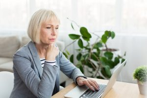 Elderly woman writer working on new article, using laptop computer